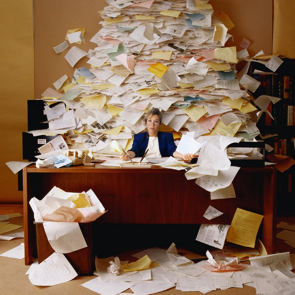 paper_piled_behind_desk
